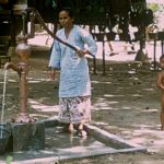 Mother pumping water from a well in a rural village