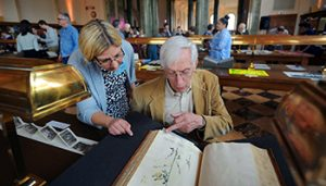 Dawne Lucas helps a patron view a historical manuscript
