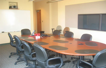large desk with chairs, a white board, and video screens