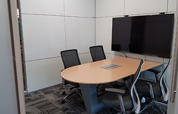 Display screen above a desk with four chairs